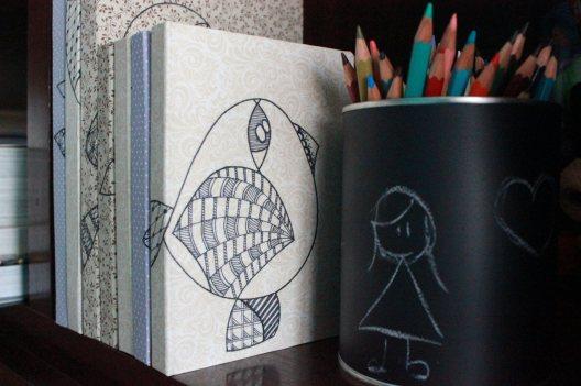 Encadernações artesanais com capas desenhadas a mão.