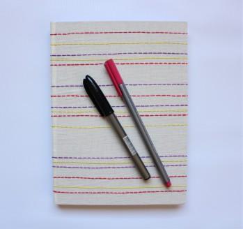Encadernação artesanal com capa bordada a mão.